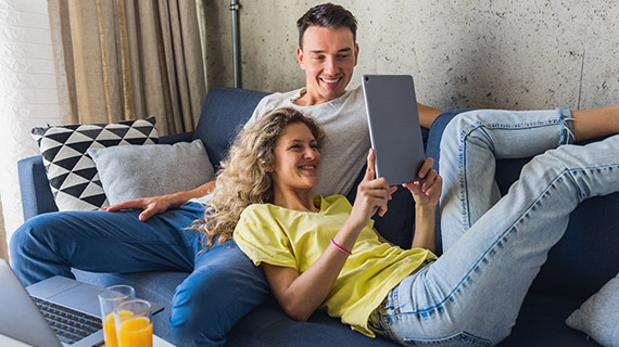 Couple smiling while looking at a tablet together on a couch