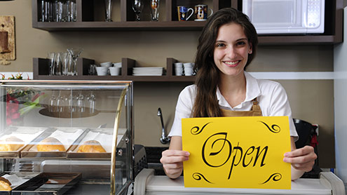 """Female barista holding """"Open"""" sign"""
