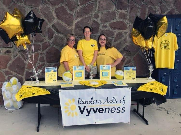 Vyve employees pose at a table during Shawnee Splash!