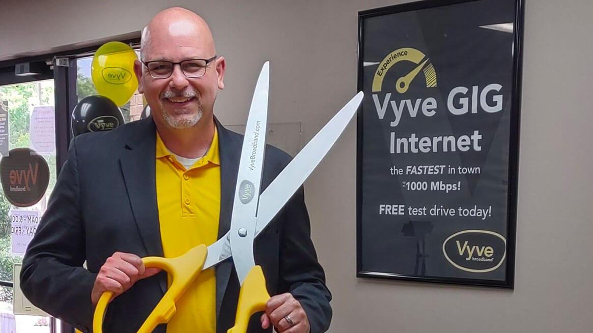 Vyve Sales team member posing with oversized scissors