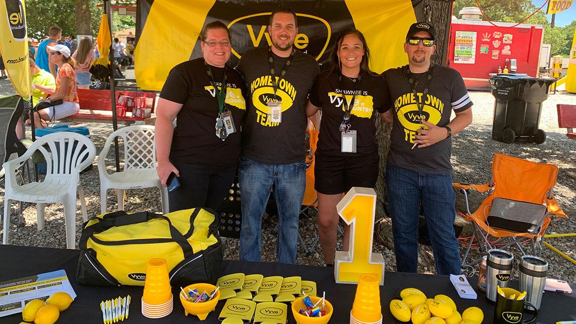 Vyve Sales team members pose behind a table of Vyve swag
