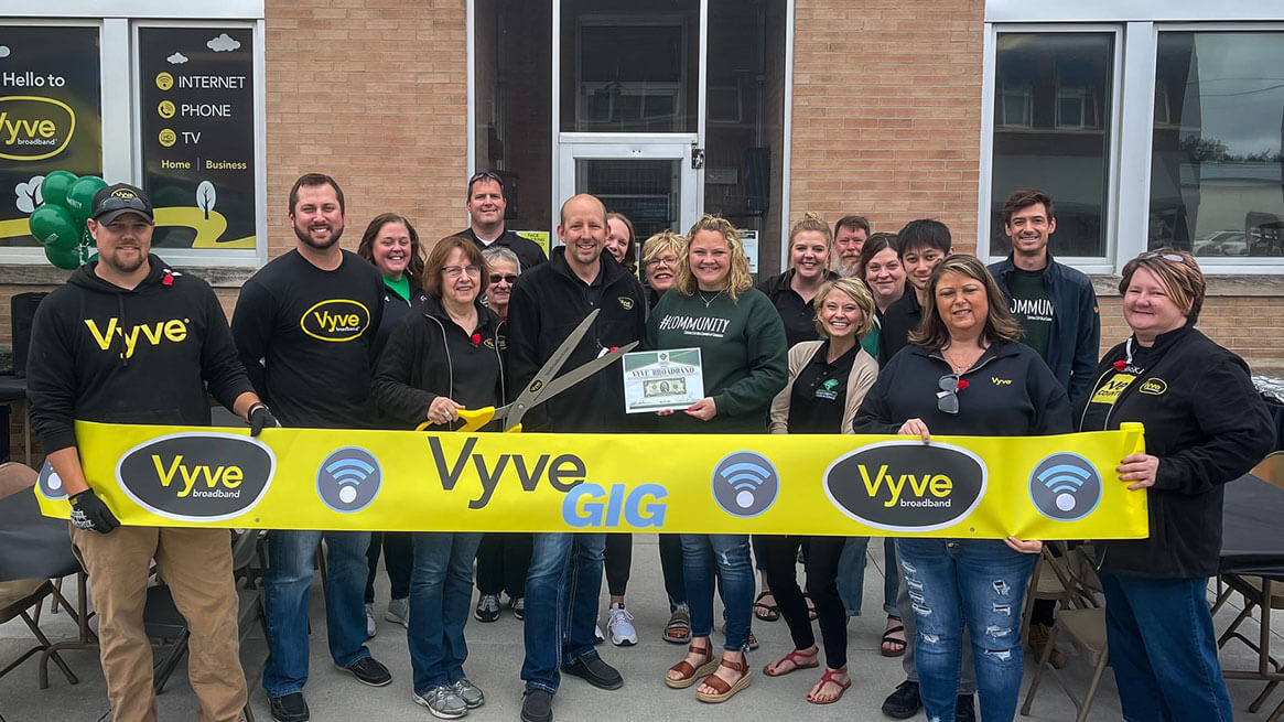 Vyve team members posing with yellow Vyve Gig banner